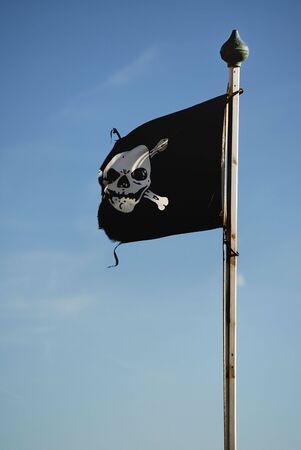 flagpoles: Skull and cross bones flag on a flagpole set against a blue sky Stock Photo