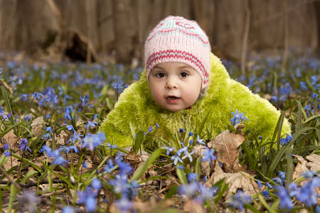 A girl   child  lying in the flowers in spring forest