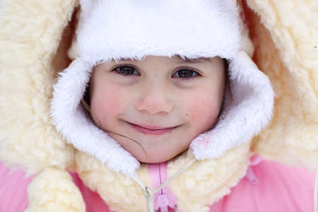 A portrait of the smiling girl wearing a bright pink coat and white fur hat