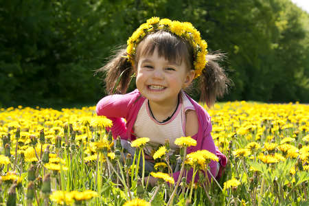 A smiling girl sitting on the dandelion field with the dandelion garland