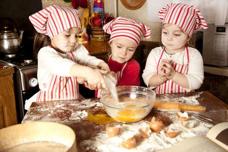 children cooking: Tres peque�os chefs que disfrutan en la cocina preparando las chicas grandes poco l�o haciendo pan en la cocina Foto de archivo