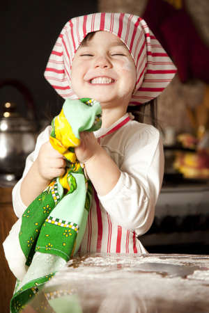 messy kitchen: little chef in the kitchen wearing an apron and headscarf Stock Photo