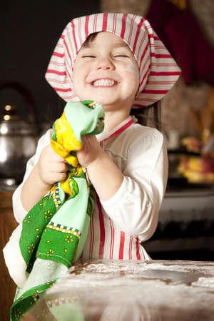 petit chef dans la cuisine portant un tablier et un foulard