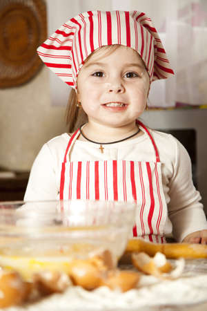 making fun: little chef in the kitchen wearing an apron and headscarf Stock Photo