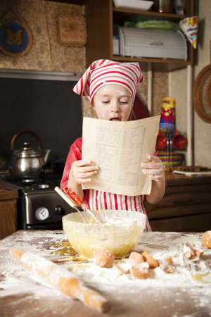 little chef in the kitchen wearing an apron and headscarf Stock Photo