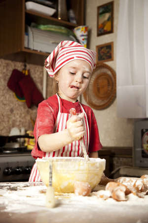 little chef in the kitchen wearing an apron and headscarf photo