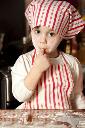 messy kids: little chef in the kitchen wearing an apron and headscarf Stock Photo