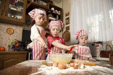 haciendo pan: Tres cocineros peque�os disfrutan en la cocina haciendo las chicas grandes poco l�o haciendo pan en la cocina Foto de archivo