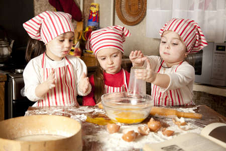 messy kitchen: Three little chefs enjoying in the kitchen making big mess  Little girls making bread in the kitchen