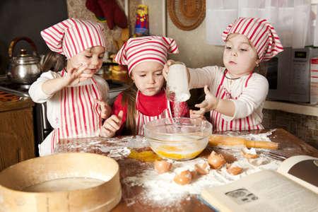 making bread: Tre piccoli cuochi godono in cucina a preparare le ragazze a Little Big Mess fare il pane in cucina