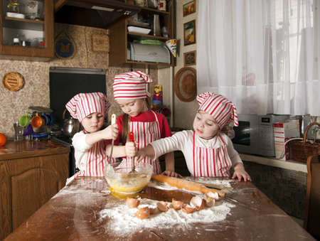 Three little chefs enjoying in the kitchen making big mess. Little girls making bread in the kitchen photo