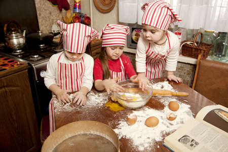 Three little chefs enjoying in the kitchen making big mess  Little girls making bread in the kitchen photo