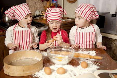 haciendo pan: Tres peque�os chefs que disfrutan en la cocina preparando las chicas grandes poco l�o haciendo pan en la cocina Foto de archivo