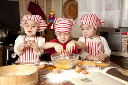 making bread: Tre piccoli cuochi che godono in cucina a preparare le ragazze gran casino Piccoli fare il pane in cucina Archivio Fotografico