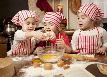 Three little chefs enjoying in the kitchen making big mess  Little girls making bread in the kitchen