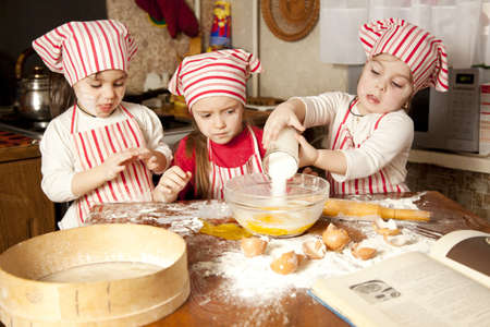 ni�os cocinando: Tres peque�os chefs que disfrutan en la cocina preparando las chicas grandes poco l�o haciendo pan en la cocina Foto de archivo
