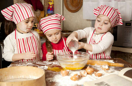 mess: Three little chefs enjoying in the kitchen making big mess  Little girls making bread in the kitchen