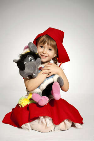 little red riding hood: Una ni�a con juguete lleva un lobo peque�o disfraz de Caperucita Roja Foto de archivo