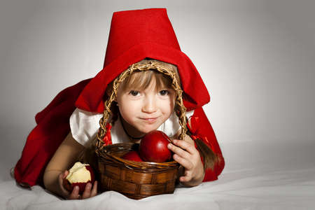 girl in red dress: A girl with a basket of red apples wearing Little Red Riding Hood costume Stock Photo