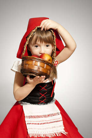 red riding hood: AA girl with a basket of red apples wearing Little Red Riding Hood costume