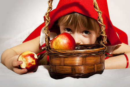 Girl dressed as Little Red Riding Hood eating an apple