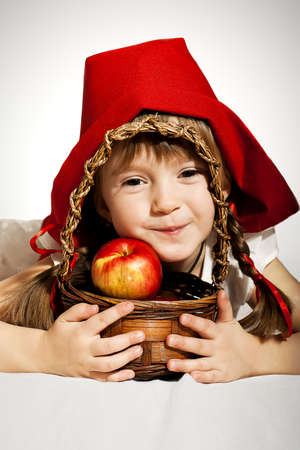 amiable: A girl with a basket of red apples wearing Little Red Riding Hood costume Stock Photo