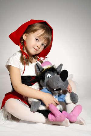 una nia con juguete lleva un lobo pequeo disfraz de caperucita roja photo