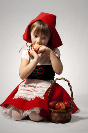 seduction: A girl with a basket of red apples wearing Little Red Riding Hood costume Stock Photo