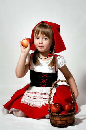 genial: A girl with a basket of red apples wearing Little Red Riding Hood costume Stock Photo