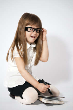portrait of the little girl wearing glasses with notebook