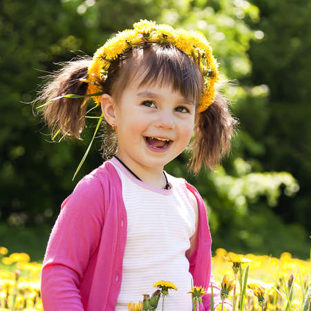 A smiling girl sitting on the dandelion field with the dandelion garland Stock Photo