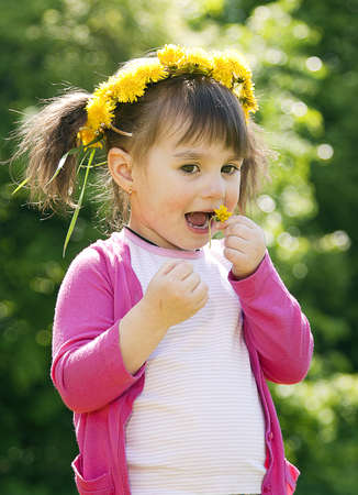 A smiling girl wearing a pink shirt with the dandelion garland Stock Photo - 12973373