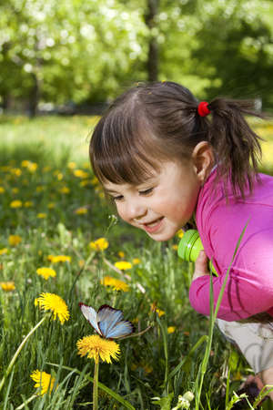 A smiling girl wearing a pink shirt, sitting on the dandelion field and observing a butterfly photo