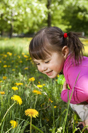 A smiling girl wearing a pink shirt, sitting on the dandelion field and observing a flower