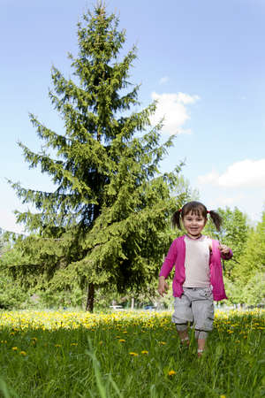 A smiling girl wearing a pink shirt, runiing across the dandelion field Stock Photo - 12973260