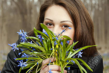 A girl   young woomen with bunch of bluebells in spring forest Stock Photo