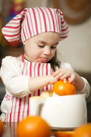 Little girl making fresh and healthy orange juice with kitchen appliance photo