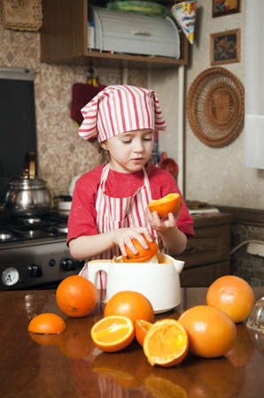 Little girl making fresh and healthy orange juice with kitchen appliance Stock Photo - 12975147