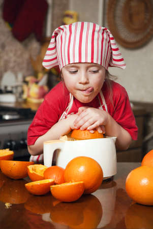 Little girl making fresh and healthy orange juice with kitchen appliance Stock Photo - 12975139