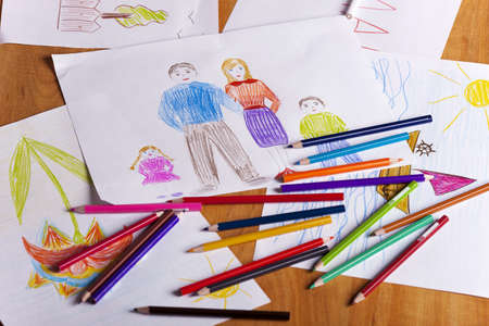 children s drawings and color pencils on the table