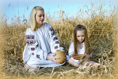 girl sitting with a child in a wheat field in traditional costumes