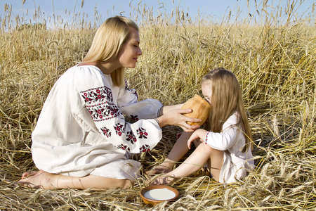 woman  watered the child in a wheat field in traditional costumes Stock Photo
