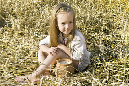child sitting on a the field of wheat ears in national dress with a milks pitcher