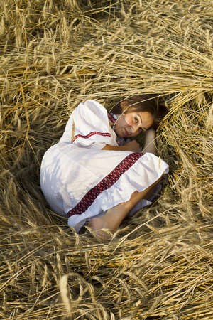 young brown-haired women lying on a field of wheat ears in national dress photo