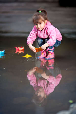 little girl, wearing a pink jacket, playing with colorful paper ship, in the puddle photo