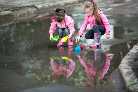 little girls, wearing a pink jacket, playing with colorful paper ship, in the puddle