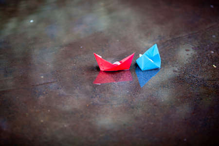 colorful paper ship, in the puddle