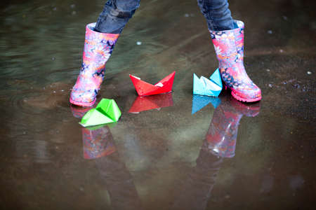 Variegated rain boots in puddle with colorful paper ship