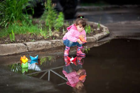 little girl, wearing a pink jacket, playing with colorful paper ship, in the puddle Stock Photo
