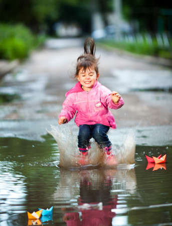happy little girl, wearing a pink jacket,  jumps into a puddle photo